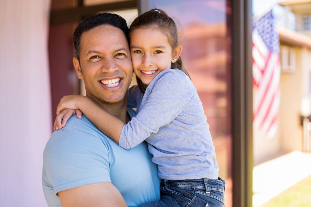 father holding preteen daughter smiling after winning child custody