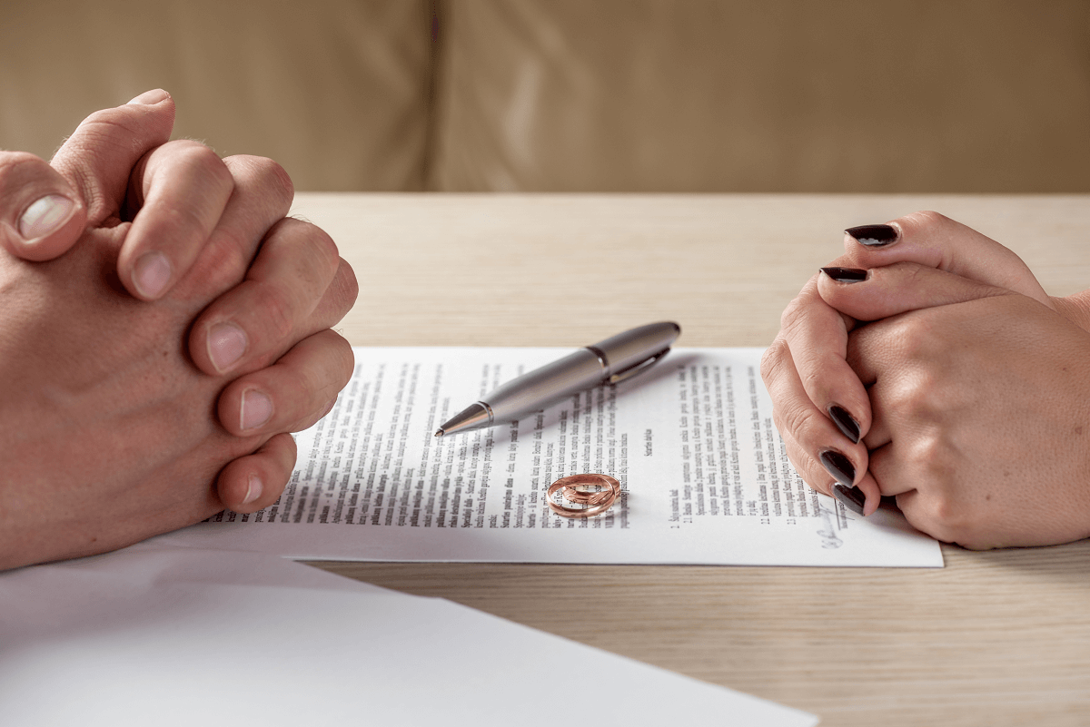 separated couples' hands and rings after signing divorce papers