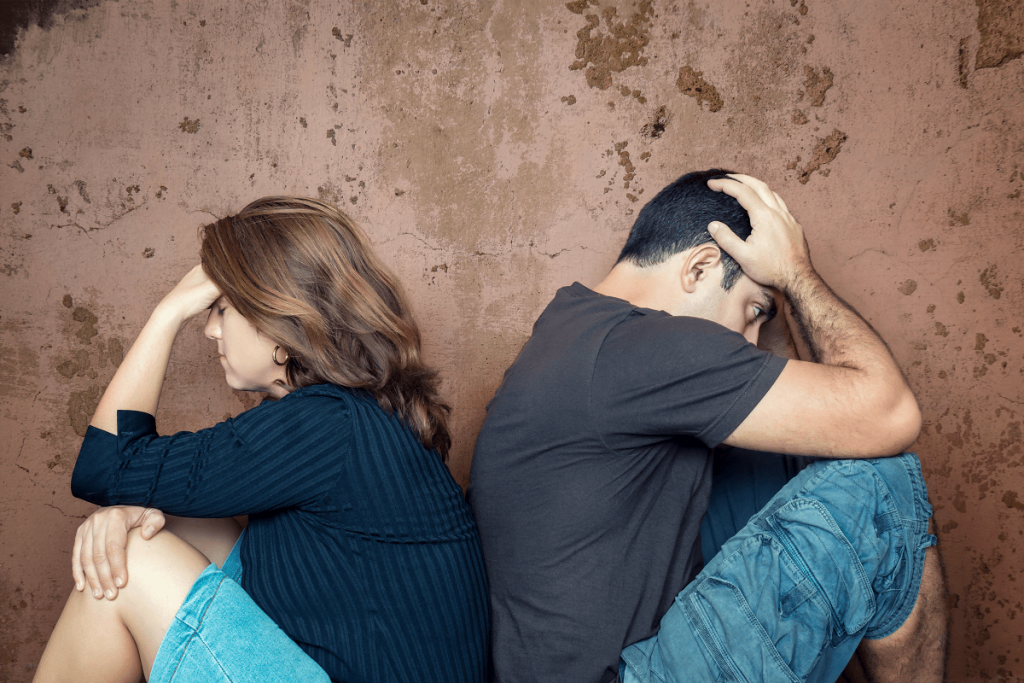 distraught couple siting back-to-back considering divorce