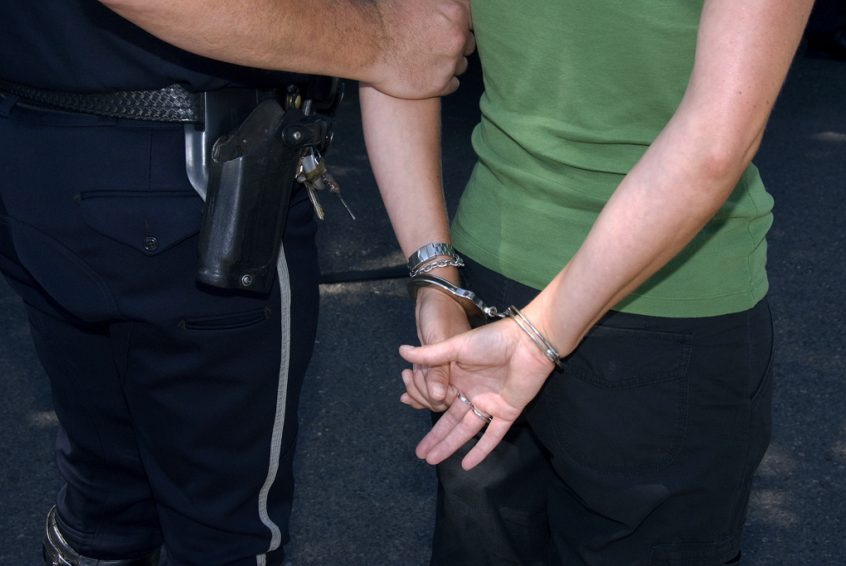 woman arrested in handcuffs in police officer's control